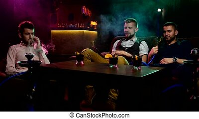 Boys smoking hookah in the caffee - Group of young and sexy...