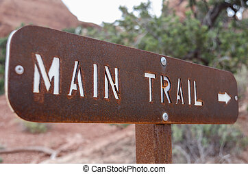 Main Trail Sign - A brown metal sign directs hikers to the...