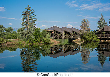 Bridge Over Calm Pond - A covered bridge over a calm pond in...