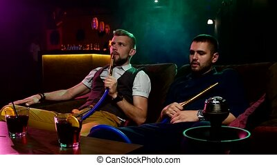 men smoke from shisha pipei n the lounge caffee - two young...
