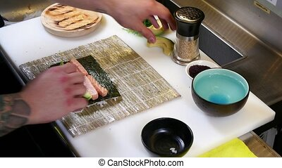 Sushi Chef Preparing Salmon Roll - A sushiman cooking salmon...