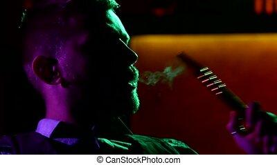 Close-up of man smoking traditional hookah pipe. man...