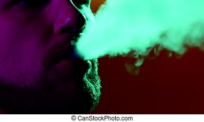 Close-up of man smoking traditional hookah pipe man exhaling...