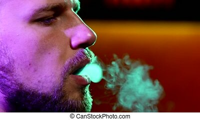 Close-up of man with a beard smoking traditional hookah pipe...