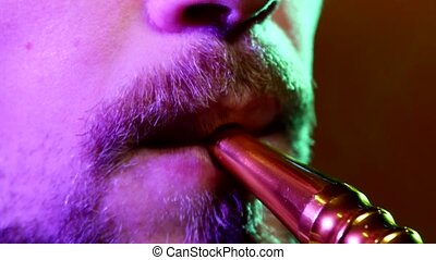 The mouth of a man smoking the traditional hubble-bubble or...