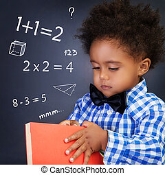 Little boy on math lesson, holding in hands book and...