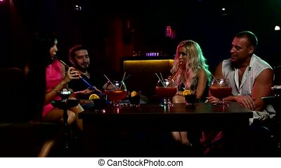 Group of young and sexy people smoking hookah in the lounge...