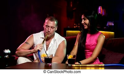 couple smoke from shisha pipe - two young people smoke from...