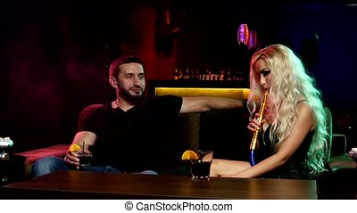 couple smoke from shisha pipe. couple talking - two young...