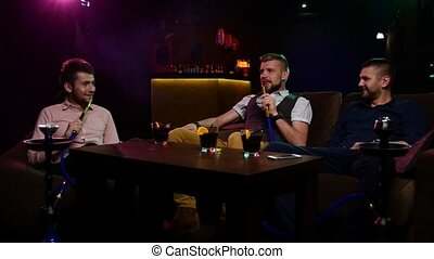 Group Boys smoking hookah in the lounge caffee. Slow motion...