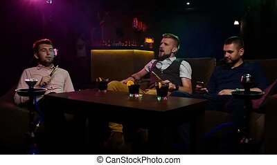 Boys smoking hookah in the lounge caffee. Slow motion -...