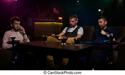 Boys smoking hookah in the caffee. Slow motion - Group of...