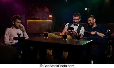 Boys smoking hookah in the lounge caffee Slow motion - Group...