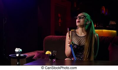 young girl with glasses resting in the hookah room. Slow...