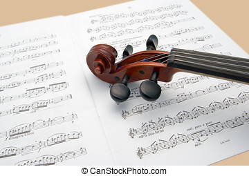 Violin neck resting on sheet music - Violin neck resting on...