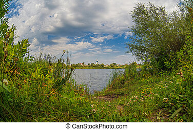 Russian summer landscape of the river and blue sky with clouds