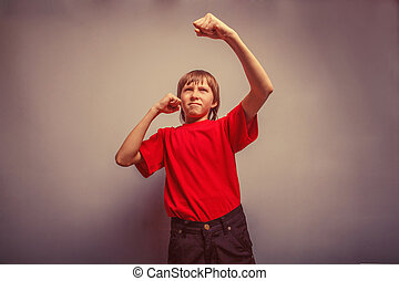 Boy, teenager, twelve years in red shirt, showing his fists...