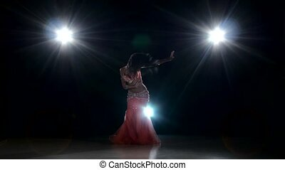 Beautiful exotic belly dancer woman dancing on black, back light