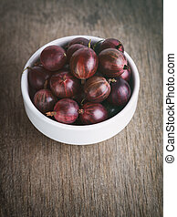 gooseberries in a bowl on a wood background, vintage toned