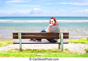 Young Woman on bench, looking out to sea