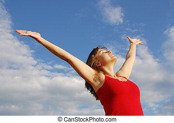 Young woman enjoying life outddors with hands to the sky