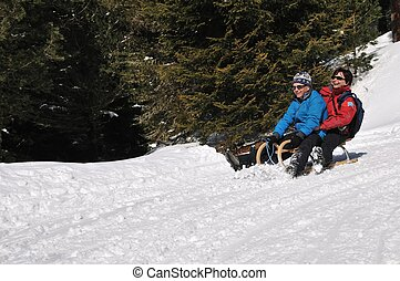 Senior couple on sledge having fun - Active senior couple on...