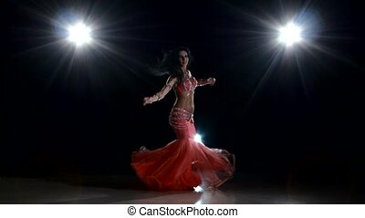 Beautiful slim woman belly dancer dancing, on black, back light