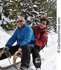 Senior couple on sledge enjoying life - Lifestyle shot of...