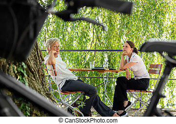 younger and older business woman sitting in a beer garden...