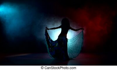 Beautiful girl in blue dancing belly dance, on red, blue,...
