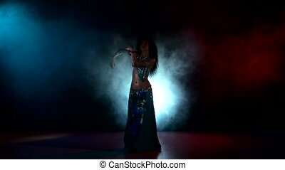 Beautiful exotic belly dancer woman dancing on red, blue, smoke, back light