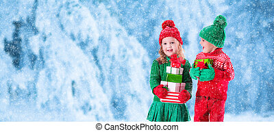 Kids with Christmas presents in snowy winter park - Little...
