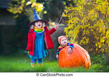 Kids trick or treating at Halloween - Little girl in witch...