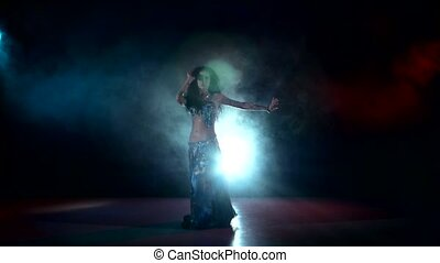 Beautiful belly dancer woman dancing exotic dancce on red, blue, smoke, back light
