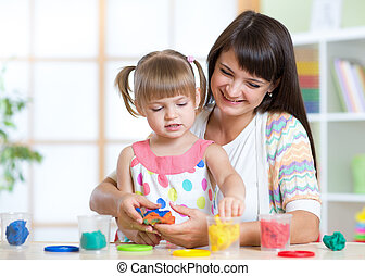 Happy child and mother sitting at table and playing with colorful clay toy