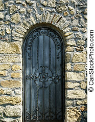 old iron door in the ancient stone wall - old iron door with...