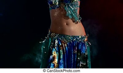 Beautiful sexy woman belly dancer in blue dress on black, back light
