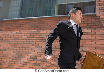 Chinese young businessman running in a city street - The...
