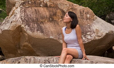 girl sits on rock admires scenery of stones and mountain stream
