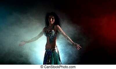 Beautiful brunette starting dancing belly dance, on black,...