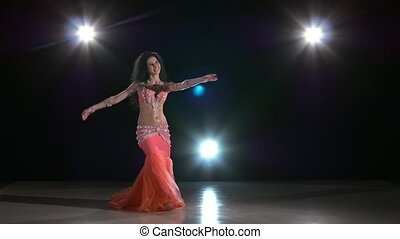 Beautiful belly dancer perfoming exotic dance in pink dress,...