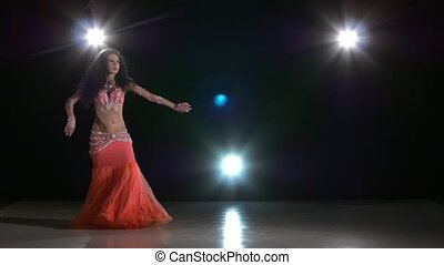 Sexy belly dancer perfoming exotic dance in pink dress, on...