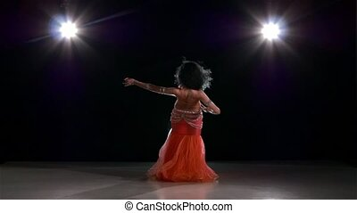 Attractive dancing belly dancer girl on black, back light,...