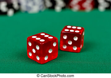 two red dice on green table