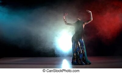 Brunette woman continue performing belly dance, on red, blue, smoke, slow motion