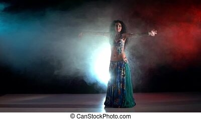 Brunette woman go on performing belly dance, on red, blue, smoke, slow motion