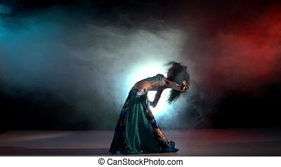 Brunette woman go on performing belly dance movements, on red, blue, smoke, slow motion