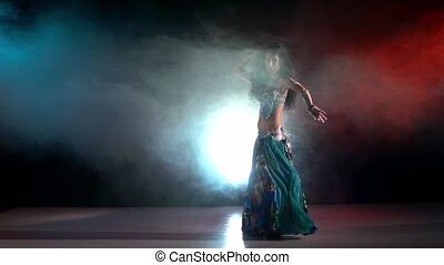 Brunette woman performing belly dance dancing in smoke, on red, blue, slow motion
