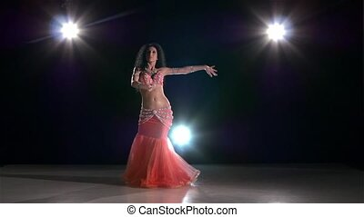 Young dancing belly dancer girl on black, back light, slow...