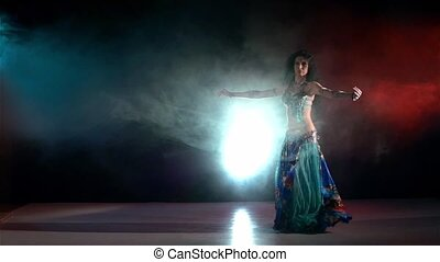 Beautiful slim woman belly dancer sexy dancing on blue, red, in smoke, slow motion